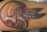 Schaedel und feder tattoo arm