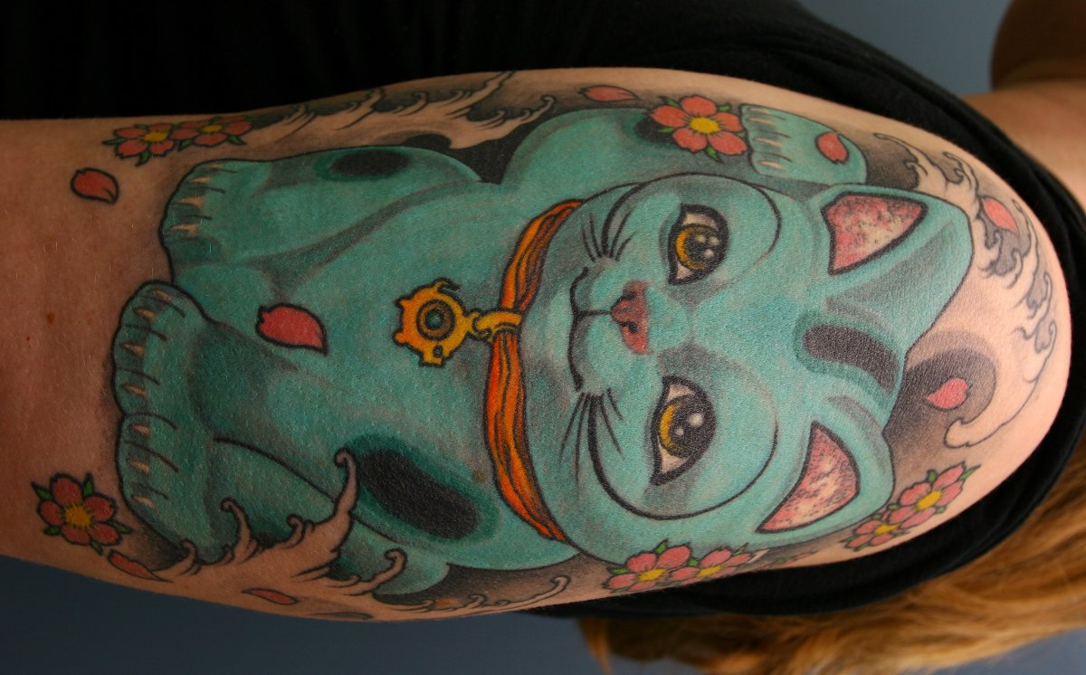 Glueckliche-Katze-Tattoo-am-Oberarm