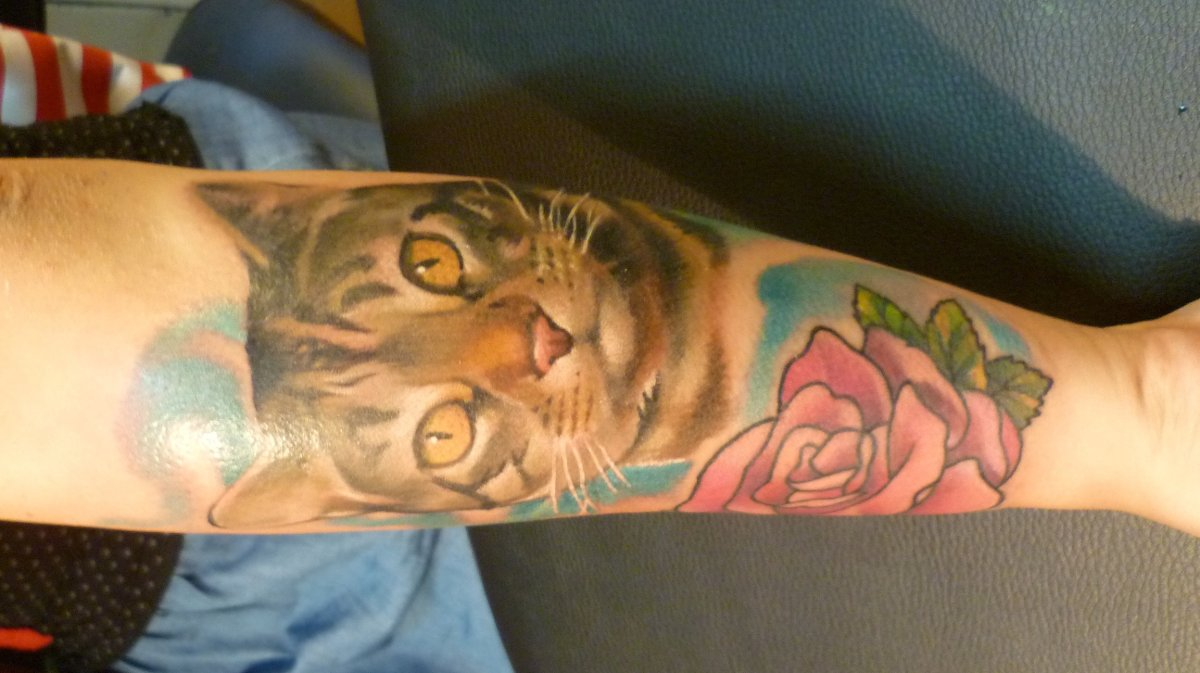 Katze-mit-Blumen-Tattoo-am-Oberarm